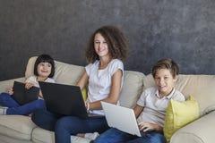 Tableta y ordenador portátil del wirh de la muchacha de la niña, del muchacho adolescente y del pelo rizado Foto de archivo libre de regalías
