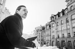 Tableta y periódico, día de la tenencia del hombre de negocios al aire libre, blancos y negros Foto de archivo