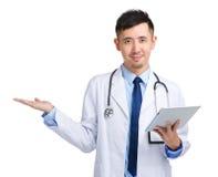 Tableta y presente de la tenencia del médico algo fotografía de archivo