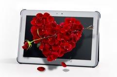 Tableta y rosas Fotos de archivo libres de regalías