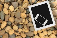 Tableta y smartphone en el piso de piedra Imagen de archivo libre de regalías