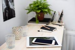 Tableta y smartphone en la tabla de funcionamiento Fotografía de archivo