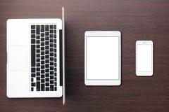 Tableta y teléfono del ordenador portátil en la visión de escritorio Imágenes de archivo libres de regalías