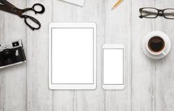 Tableta y teléfono elegante con la pantalla blanca para la maqueta imagenes de archivo