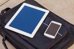 Tableta y teléfono móvil en un bolso de moda Copie el espacio aventaje Foto de archivo
