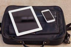 Tableta y teléfono móvil en un bolso de moda Copie el espacio aventaje Imagen de archivo