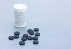 Tabletas activadas del carbón de leña para limpiar el cuerpo en Gray Background Closeup Fotografía de archivo