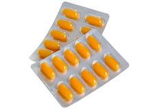 Tabletas amarillas de las píldoras en la ampolla brillante en un fondo blanco Imágenes de archivo libres de regalías