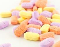 Tabletas antibióticos coloridas en blanco Imágenes de archivo libres de regalías