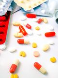 Tabletas blancas y coloridas de la medicación en el fondo blanco imagen de archivo