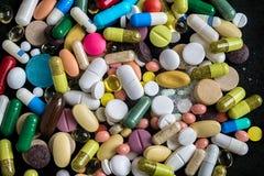 Tabletas, cápsulas, drogas de la terapia y píldoras farmacéuticas en fondo negro imágenes de archivo libres de regalías