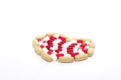 Tabletas coloridas dispuestas en forma del corazón Fotografía de archivo