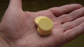 Tabletas de vitamina en la palma masculina almacen de metraje de vídeo