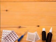 Tabletas, descensos, herbals y termómetro en un fondo de madera Foto de archivo libre de regalías