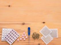 Tabletas, descensos, herbals y termómetro en un fondo de madera Fotos de archivo libres de regalías