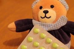 Tabletas medicinales con un juguete suave Imagenes de archivo