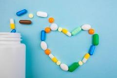 Tabletas multicoloras y cápsulas en forma de corazón, botella blanca para las tabletas, píldoras farmacéuticas de la medicina en  foto de archivo libre de regalías