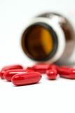 Tabletas rojas del suplemento y la botella Foto de archivo
