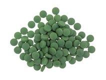 Tabletas verdes del suplemento del hierro en un fondo blanco Imágenes de archivo libres de regalías