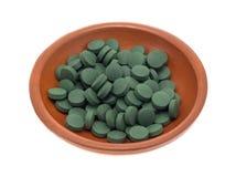 Tabletas verdes del suplemento del hierro en un pequeño cuenco Foto de archivo