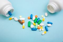 Tabletas y cápsulas multicoloras, botella blanca para las tabletas, píldoras farmacéuticas de la medicina en el fondo azul, una a imagen de archivo