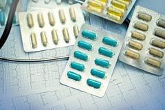 Tabletas y cápsulas de las medicaciones en el primer de la tabla Fotografía de archivo