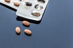 Tabletas y paquete de ampolla ovales medicinales en el fondo de cristal Fotografía de archivo