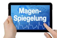 Tabletcomputer met het Duitse woord voor gastroscopy - Magenspiegelung stock afbeeldingen