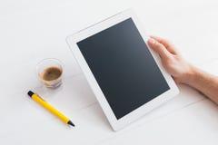 Tabletgerät über einer weißen hölzernen Arbeitsplatztabelle Stockfotografie