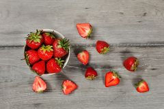 Tabletop άποψη - το μικρό κεραμικό κύπελλο των φραουλών, περισσότεροι έκοψε τα φρούτα γύρω στο γκρίζο ξύλινο γραφείο στοκ εικόνες