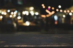 Tabletop de madeira vazio com fundo da luz do mercado da noite do borrão foto de stock