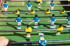 Tabletop football game with a green field and blue and yellow rivals stock photo