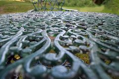 Tabletop intrincadamente ornamented do ferro fundido em um jardim imagem de stock