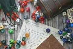 Tabletop roleplaying flat lay with colorful RPG and game dices,  character sheet, rule book and treasure chest