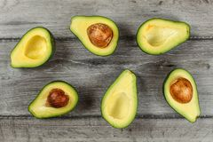 Tabletop view - arranged avocado halves, some of them with the s. Eed, on gray wood desk stock images