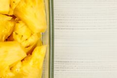 Tabletop view, detail - yellow pineapple cut in pieces, in square glass bowl, white boards desk / space for text on right. Tabletop view, detail - yellow stock image