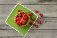 Tabletop view, small basket full of strawberries, some of them s. Pilled on green table cloth under it stock photos