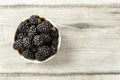 Tabletop view, small ceramic cup with blackberries on gray wood desk. Space for text on the right.  royalty free stock photos
