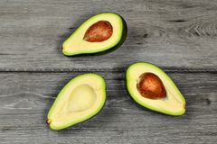 Tabletop view - three halves of cut avocado, some with seed pit,. On gray wood desk royalty free stock images