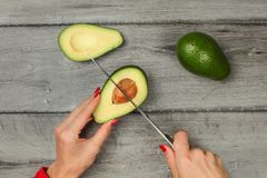 Tabletop view - woman hand holding chef knife, removing seed fro. M avocado cut in half royalty free stock images