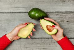 Tabletop view, woman hand holding two halves of avocado in each royalty free stock photo