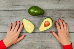 Tabletop view - woman hands with red nails, avocado cut in half, whole one above, on gray wood desk. royalty free stock photography