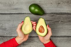 Tabletop view woman`s hand holding two avocado halves, seed visi royalty free stock photo