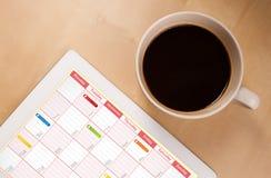 Tabletpc die kalender op het scherm met een kop van koffie op D tonen Royalty-vrije Stock Afbeeldingen
