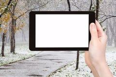Tabletpc en eerste sneeuwval in stedelijk park Stock Afbeeldingen