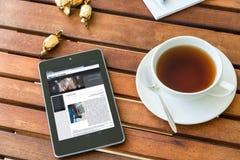 Tabletpc in koffie Stock Afbeelding