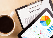 Tabletpc toont grafieken op het scherm met een kop van koffie op een bureau Royalty-vrije Stock Foto