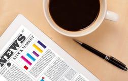 Tabletpc toont nieuws op het scherm met een kop van koffie op een bureau Stock Foto's