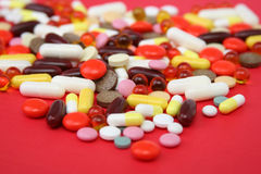 Tablets. Vitamins multi-coloured on red background Stock Photo