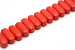 Tablets. Red greater tablets laid out accurately in one line Royalty Free Stock Photography